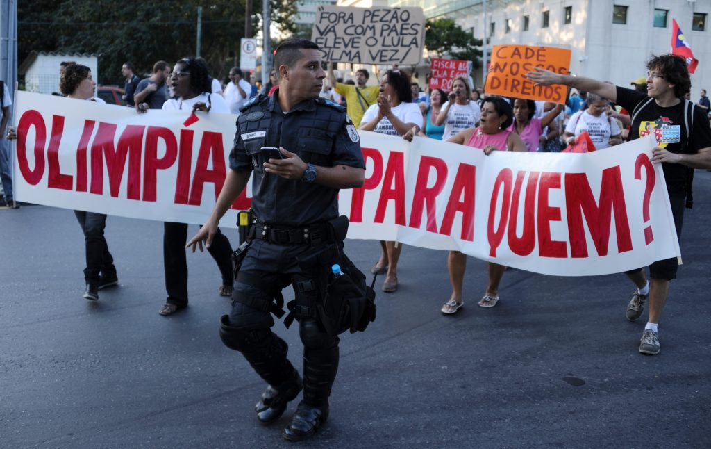 """Demonstrators hold a banner reading """"Olympics for whom?"""""""
