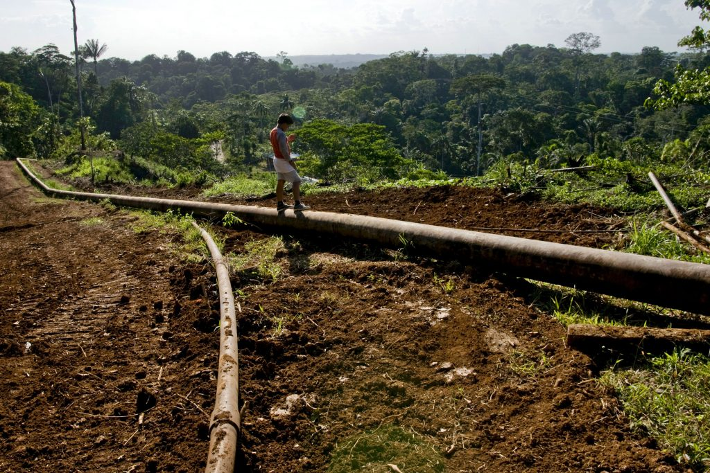 A child from the Huaorani tribe, who are native Amerindians from the Amazonian Region of Ecuador, stands on an oil pipeline belonging to China's PetroOriental SA in Yasuni National Park in Orellana Province, Ecuador, on Tuesday, Oct. 13, 2009. Ecuador is seeking about $3 billion in revenue, almost half earlier government estimates, in a bid to keep oil inside Yasuni National Park rather than extract it. The Ishpingo-Tambacocha-Tiputini field contains an estimated 950 million barrels of oil. Photographer: Alejandra Parra/Bloomberg